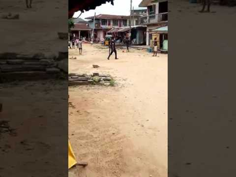 Mentally challenged man playing football on the street with kids
