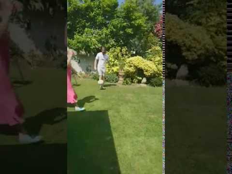 Lad playing football nutmegs his mum